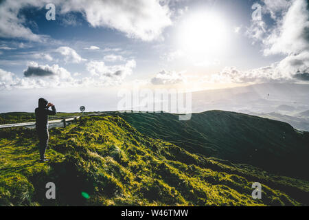 Young man tourist overlooking Beautiful panoramic view of Lagoa do Fogo, Lake of Fire, in Sao Miguel Island, Azores, Portugal. Sunny day with blue sky - Stock Photo