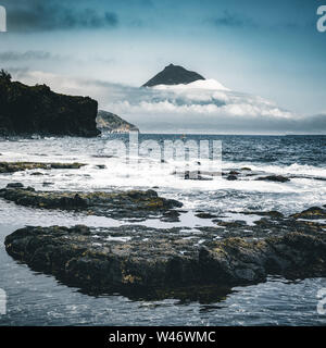 Mount Pico volcano western slope viewed from ocean with summit in clouds, seen from Faial Island in Azores, Portugal. - Stock Photo