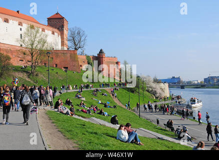 Sunday Afternoon.  People enjoying early  spring sunshine by the Royal Wawel Castle and the Vistula River, Krakow, Little Poland. - Stock Photo