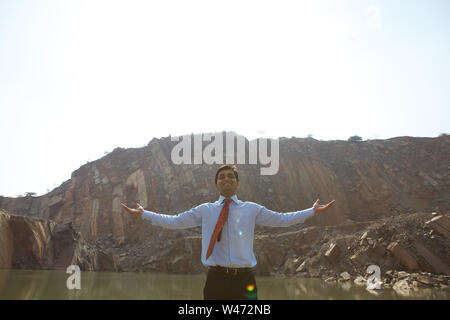 Businessman standing with his arms outstretched - Stock Photo