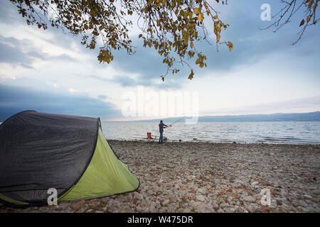 man in camp near lake, try to fishing - Stock Photo