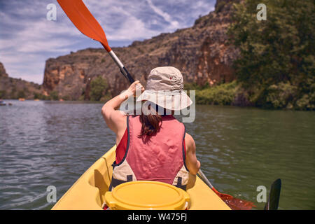 Rear view of woman while kayaking in river - Stock Photo