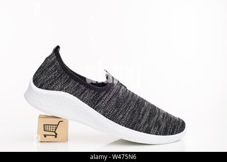 Fashionable man walking shoes with box on a white background. The concept of purchase with delivery - Stock Photo