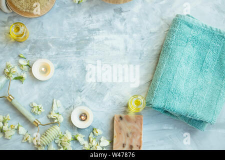 Spa still life top view setting with towel, candles. jasmine flowers, jade face roller, body oil bottle on concrete background with copy space, natura - Stock Photo