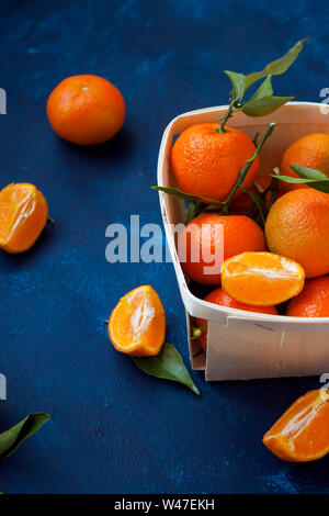 Refreshing sliced tangerines with leaves in a basket on vibrant blue background. - Stock Photo
