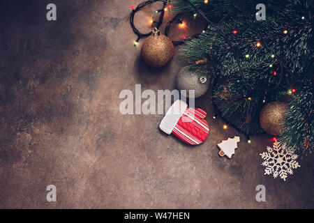 Christmas festive background, fir-tree with a garland and balls, gingerbread mitten on a dark textured rustic background. Top view, flat lay, copy spa - Stock Photo