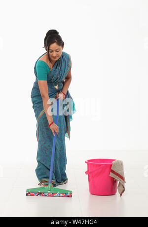 Indian young woman wiping floor - Stock Photo