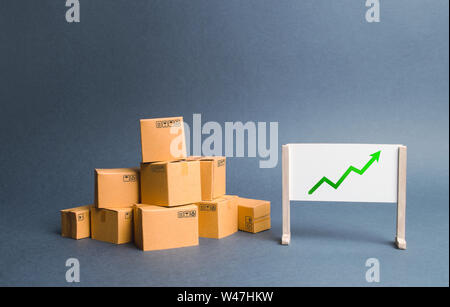 A pile of cardboard boxes and stand with green up arrow. Price increase. The growth rate of production. Increasing consumer demand. exports and import - Stock Photo