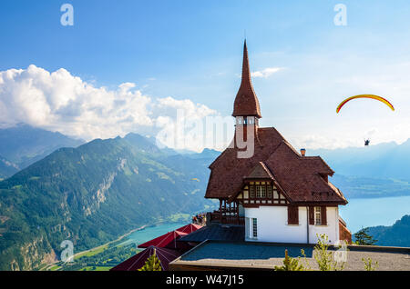Stunning view of the top of Harder Kulm in Interlaken, Switzerland photographed in summer with paragliders flying around. Hilly Alpine landscape and Lake Thun in background. Paragliding, sunset. - Stock Photo