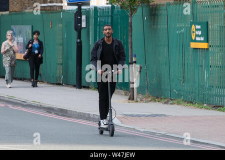 London, UK. 18 July, 2019. A man rides a Xiaomi folding electric scooter on the road in Lambeth. Credit: Mark Kerrison/Alamy Live News - Stock Photo
