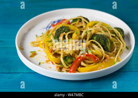 Asia food. Stir fry udon noodles with vegetables on the black table, cooked in wok - Stock Photo