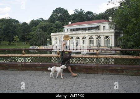 Woman walks her dog over the  Lullwater Bridge by the historic Boathouse which houses the Audubon Society in Prospect Park, Brooklyn, New York. - Stock Photo