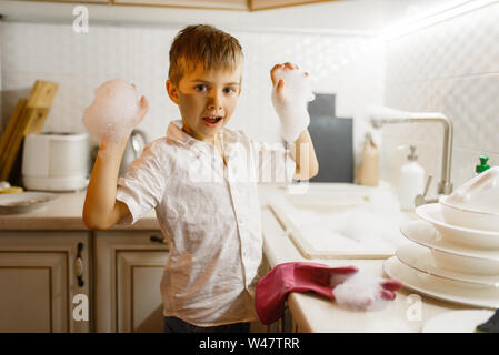 A little boy in gloves washing dishes on the kitchen. Baby doing housework at home. Young mom's helper cleans the house - Stock Photo