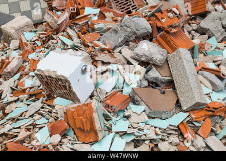Building waste dump. Bricks, tiles and concrete pieces in heap of debris. Damaged and cracked old floor and masonry from bathroom demolition. Disaster. - Stock Photo