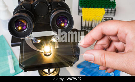 Laboratory optical microscope. Human hand holding a specimen on glass slide. Black medical scope, eyepieces, shining light rays and test tubes in rack. - Stock Photo