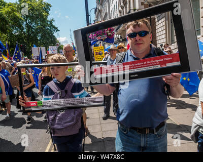 London, UK. 20th July 2019. Two marchers with TV screens as thousands march from Park Lane to a rally in Parliament Square organised by grassroots groups to urge the UK to ditch Brexit and Boris Johnson and stay in Europe. They say poll after poll shows that the public would now vote Remain, and that the leave case was full of lies, with no-one voting for the kind of disastrous no-deal Brexit that Johnson and his supporters now propose and call for a new people's vote. The UK is now a pro-EU country and should remain in full EU membership to build a cleaner, greener, safer, fairer life for all - Stock Photo