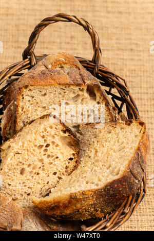 Close up of hearty artisan sourdough bread slices in a bread basket. - Stock Photo