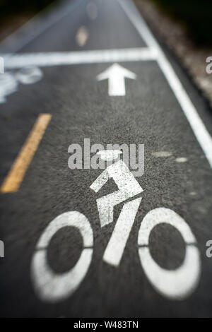 Lensbaby photo of city street with bike lane symbol painted in white - Stock Photo