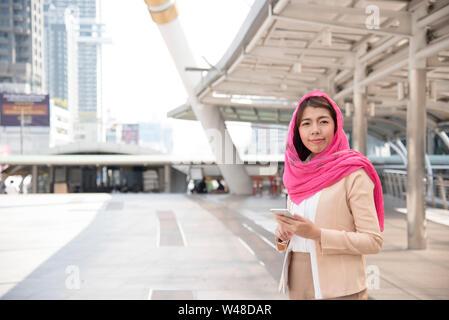 Beautiful Modern Arab Businesswoman wear hijab  Using Mobile Phone in the big city. - Stock Photo