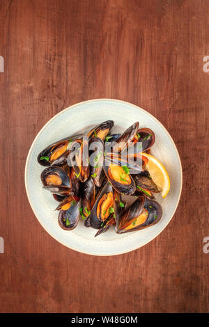 Marinara mussels, moules mariniere, shot from the top on a dark rustic wooden background with a place for text - Stock Photo
