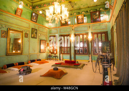 aipur, Rajasthan, India - circa 2017: Green walled room with a chandelier, lights and ground seating for royalty in Udaipur city palace. These old maj - Stock Photo