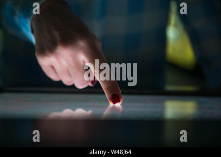 Woman using interactive touchscreen display at modern museum or exhibition - Stock Photo