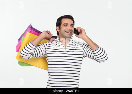 Indian young man carrying shopping bags and talking on mobile phone - Stock Photo