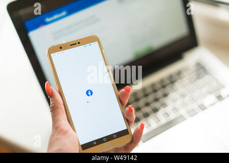 Kedainiai, Lithuania - June 25, 2019: woman hand holding Huawei smartphone with Facebook app on background of Macbook with Facebook main login page on - Stock Photo