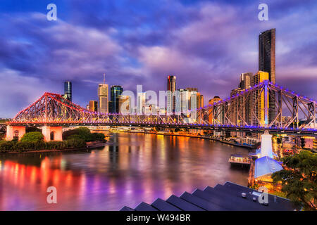 Bright lighs of Story Bridge in Brisbane city across Brisbane river in front of high-rise towers, CBD. Pre-sunrise image with reflection of illuminati - Stock Photo