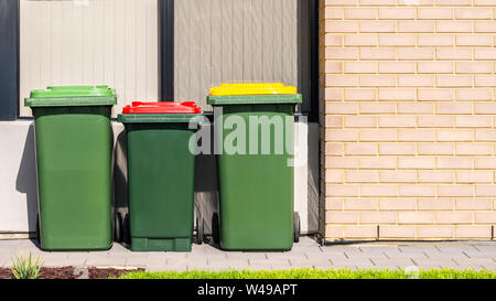 Australian garbage wheelie bins with colourful lids for recycling, general and green waste provided by local council - Stock Photo