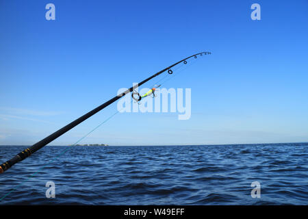 rod with crank bait for catching predatory fish aboard a boat against the blue sea and sky - Stock Photo
