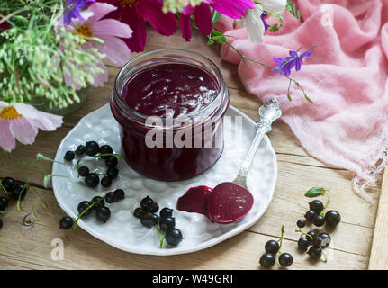 Black currant custard, currants and a bouquet of wild flowers on a wooden background. Rustic style. - Stock Photo
