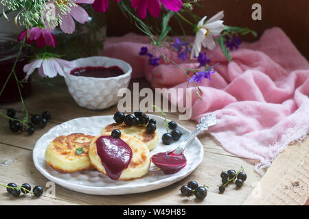 Breakfast of quark pancakes, black currant custard, currants and a bouquet of wild flowers on a wooden background. - Stock Photo