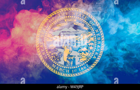 The national flag of the US state Nebraska in against a gray smoke on the day of independence in different colors of blue red and yellow. Political an - Stock Photo