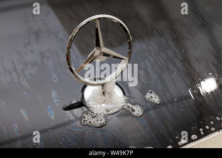 Novosibirsk, Russia - 07.19.2019: Close-up on the emblem of a car manufacturer Mercedes Benz on the hood of a black car during washing and cleaning in
