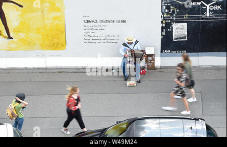 Berlin, Germany. 21st July, 2019. A street musician is playing at the East Side Gallery. Credit: Paul Zinken/dpa/Alamy Live News - Stock Photo