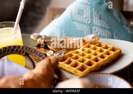 A closeup shot of waffle and pancake with berries on top near a juice - Stock Photo