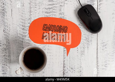 Conceptual hand writing showing Emerging Markets. Concept meaning country that has some characteristics of developed stores Wooden vintage table backg - Stock Photo