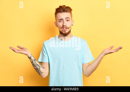 Puzzled young man in blue T-shirt full of doubts, has indecisive expression, shows uncertainty, gestures against yellow background. close up portrait. - Stock Photo
