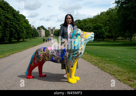 Windsor, UK. 21st July, 2019. To celebrate the 200th anniversary of the birth of Queen Victoria a pride of decorated lion sculptures will be displayed across Windsor and Maidenhead this summer raising funds for local charities. Pictured is International Jewellery Designer and Member of the Thai Royal Family, M. L. Rojanatorn na Songkhla with her jewelled lion against the backdrop of Windor Castle. Credit: Maureen McLean/Alamy Live News - Stock Photo
