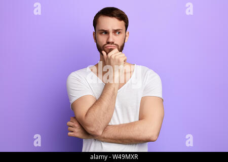 thoughtful serious frowning man touching his chin and weighs the pluses and minuses of the offer isolated on blue yellow background - Stock Photo
