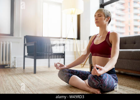 Trendy woman doing yoga as part of her mindfulness morning routine - Stock Photo
