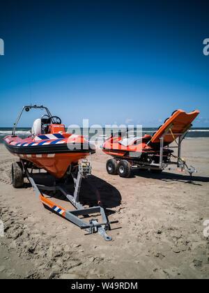 Egmond aan Zee, Netherlands - July 21, 2019: a lifesaving ship and a jetski of the dutch coastguard on the beach - Stock Photo