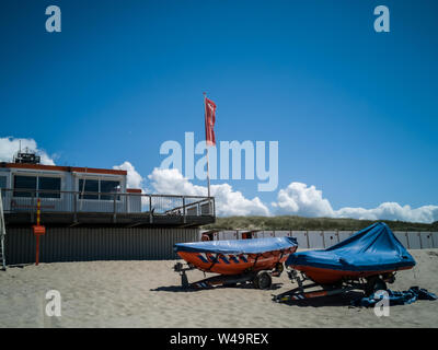 Egmond aan Zee, Netherlands - July 21, 2019: lifesaving ships of the dutch coastguard on the beach in front of the coastguard station - Stock Photo