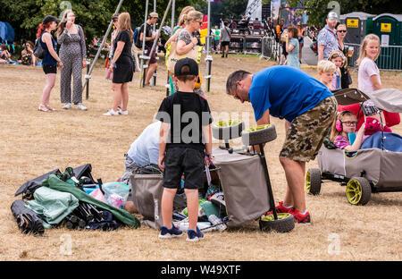Family with an overturned cart at Latitude Festival, Henham Park, Suffolk, UK, 21st July 2019 - Stock Photo