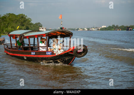 Tourists take a boat on the Mekong River. Near Cai Be floating market, Mekong delta. Tien Giang, Vietnam - Stock Photo