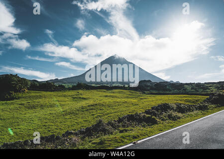 Straight EN3 longitudinal road northeast of Mount Pico and the silhouette of the Mount Pico along , Pico island, Azores, Portugal. - Stock Photo