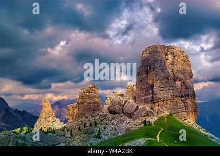 Sunrays on the dolomitic Cinque Torri (Cortina d'Ampezzo, Italy) on a cloudy day - Stock Photo