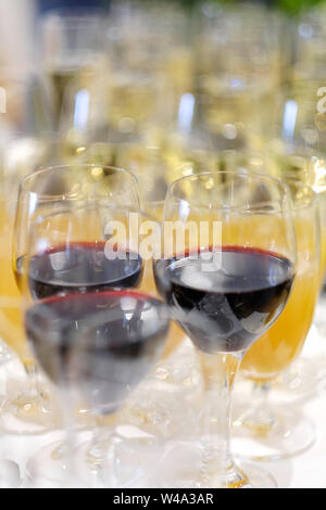 Glasses with red wine, juice and champagne on a serving table at a buffet table - Stock Photo