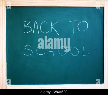 Black school chalkboard background with the inscription back the school - Stock Photo